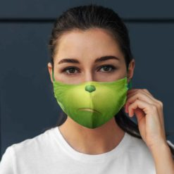 A girl wears Grinch cloth face mask